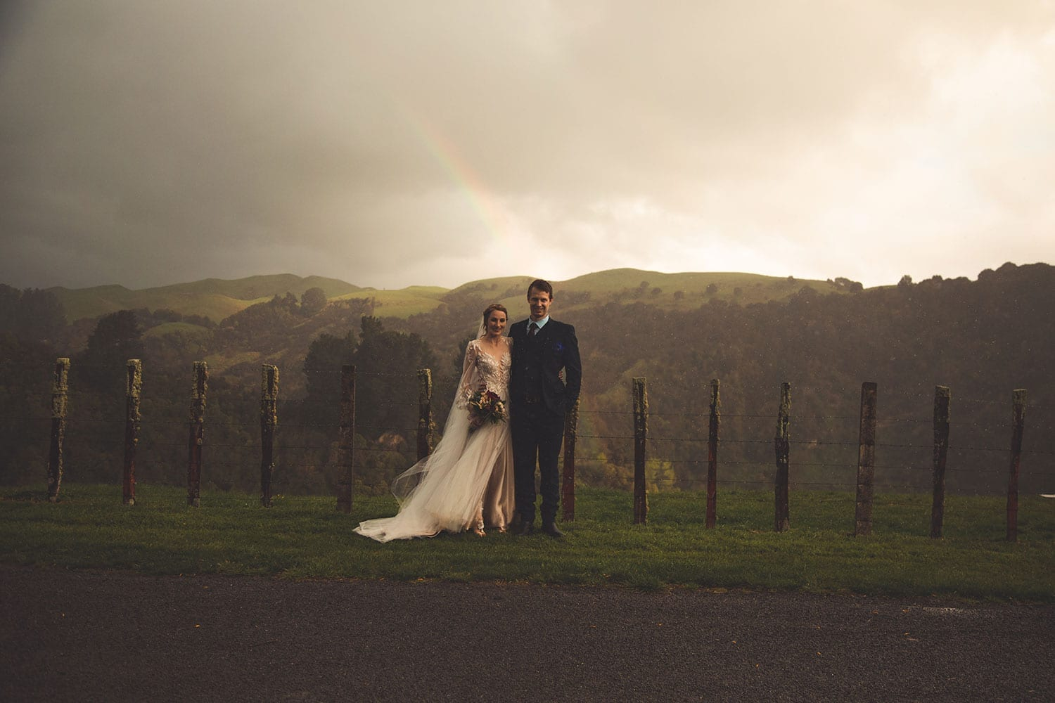 Vinka Design Features Real Weddings - bride in custom made gown, a combination of Isabelle and Ivy from our Heart of Havana collection. Bride and groom pose by outdoor fence with expansive backdrop
