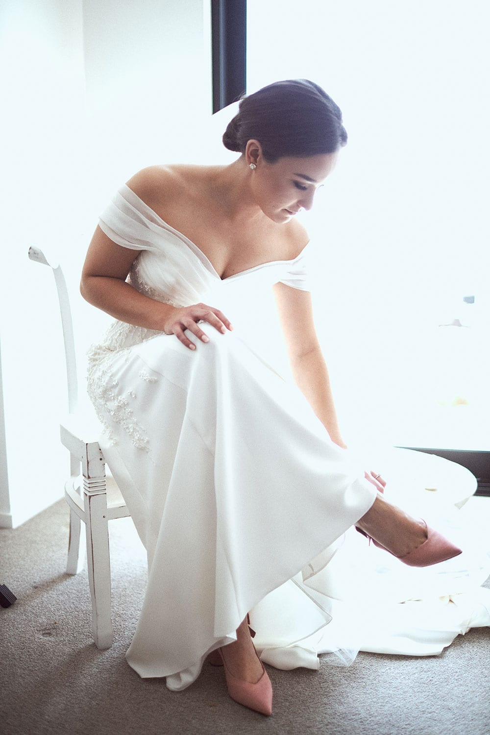Vinka Design Features Real Weddings - bride in custom made gown with stunning silhouette and lace. Bride putting on wedding shoes