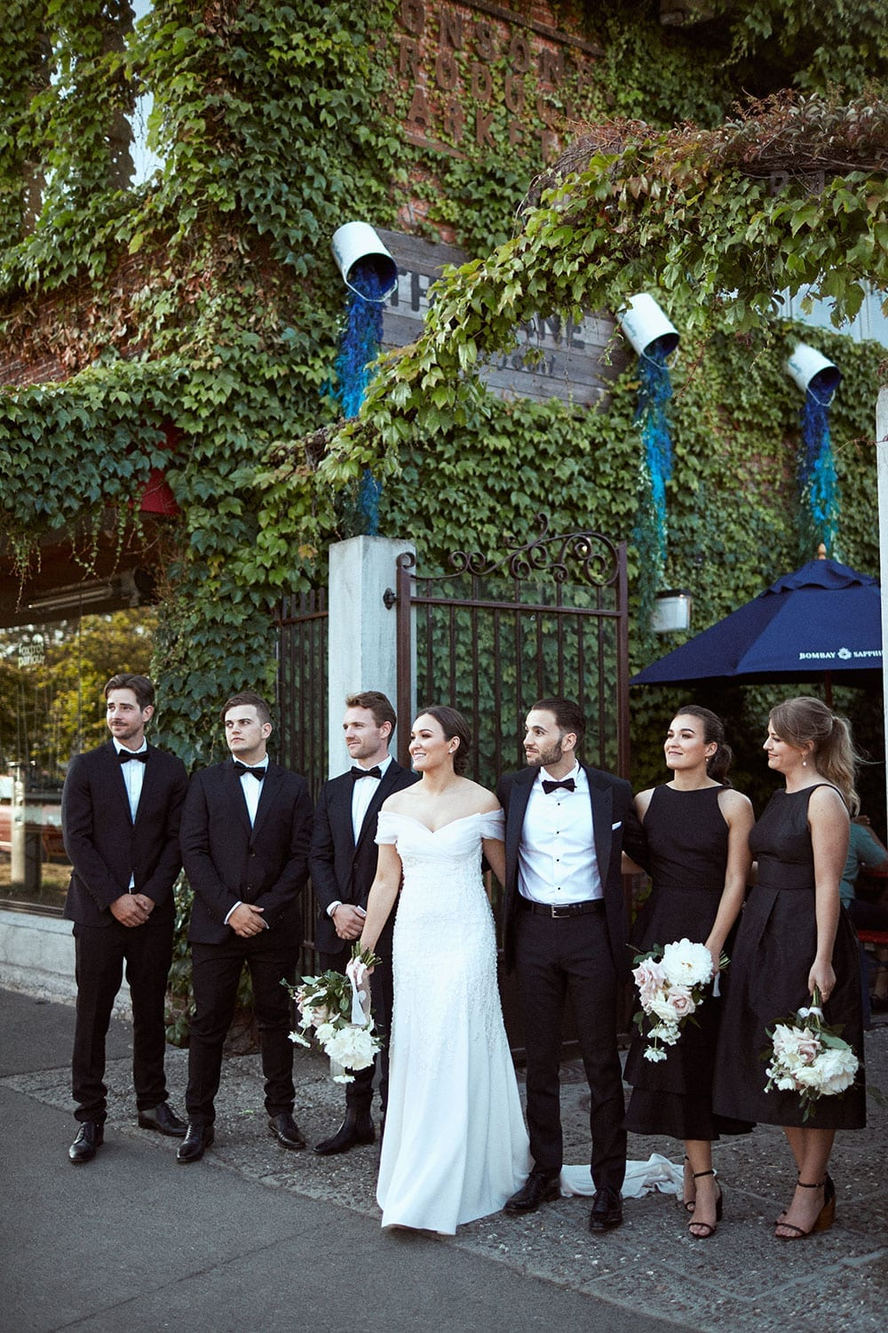 Vinka Design Features Real Weddings - bride in custom made gown with stunning silhouette. Bride and groom with bridal party outside venue