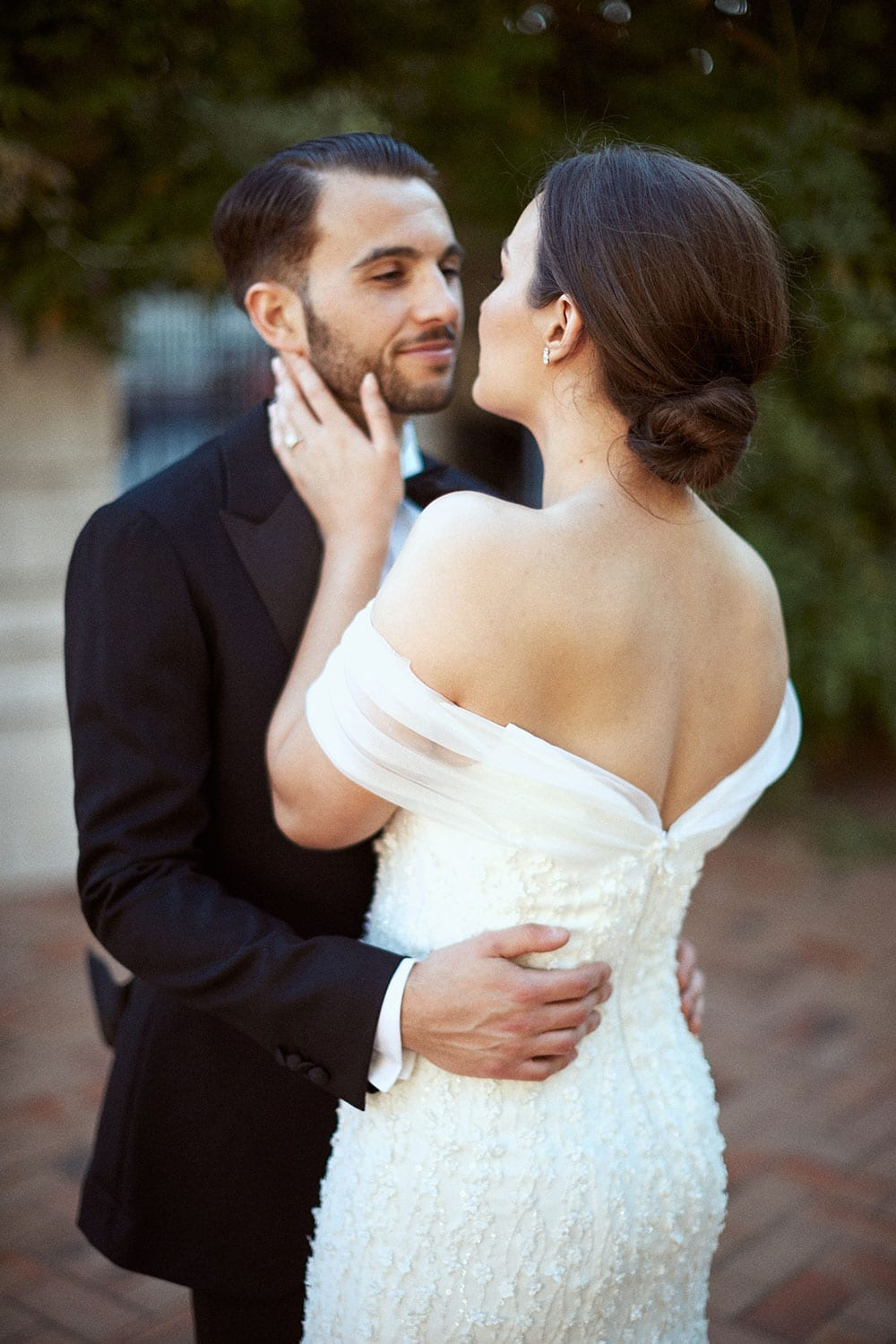 Vinka Design Features Real Weddings - bride in custom made gown with stunning silhouette and lace. Bride and groom embrace
