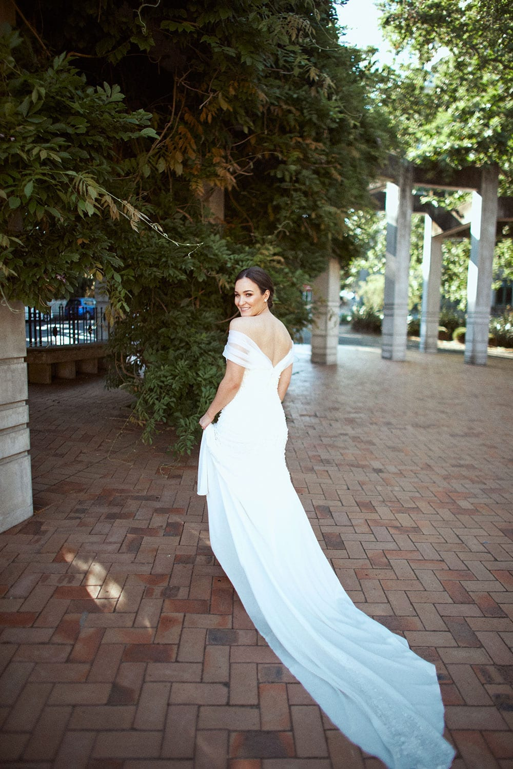Vinka Design Features Real Weddings - bride in custom made gown with stunning silhouette and lace. Bride faces away with beautiful train flowing behind