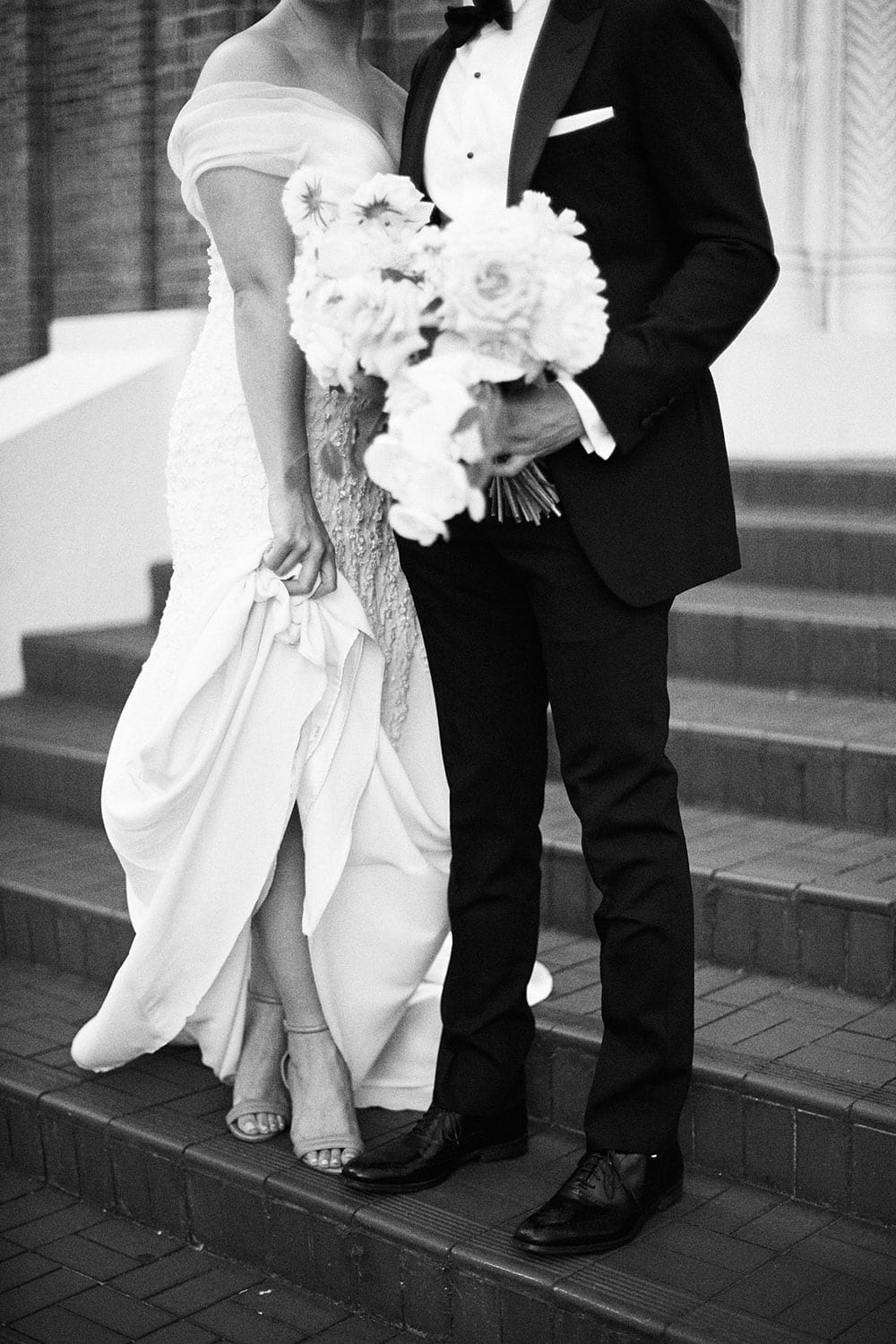 Vinka Design Features Real Weddings - bride in custom made gown with stunning silhouette with groom on steps in black and white
