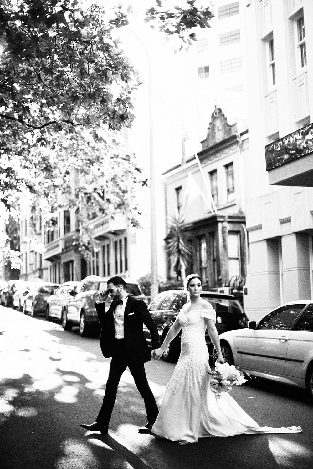 Vinka Design Features Real Weddings - bride in custom made gown with stunning silhouette. Bride and groom cross beautiful street in black and white
