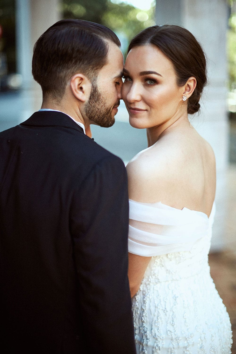 Vinka Design Features Real Weddings - bride in custom made gown with stunning silhouette. Bride and groom embrace,bride looking over shoulder with low back dress detail