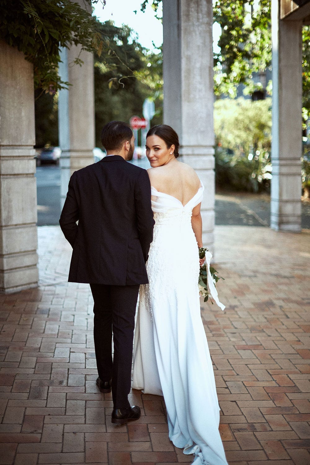 Vinka Design Features Real Weddings - bride in custom made gown with stunning silhouette. Bride and groom walking, bride looking over shoulder with low back dress detail