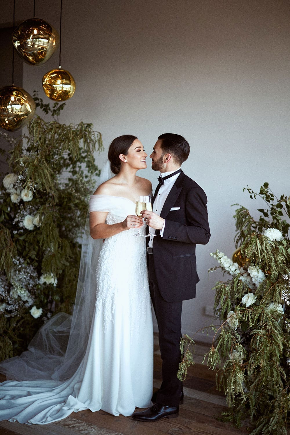 Vinka Design Features Real Weddings - bride in custom made gown with stunning silhouette. Bride and groom face to face surrounded by floral arrangements