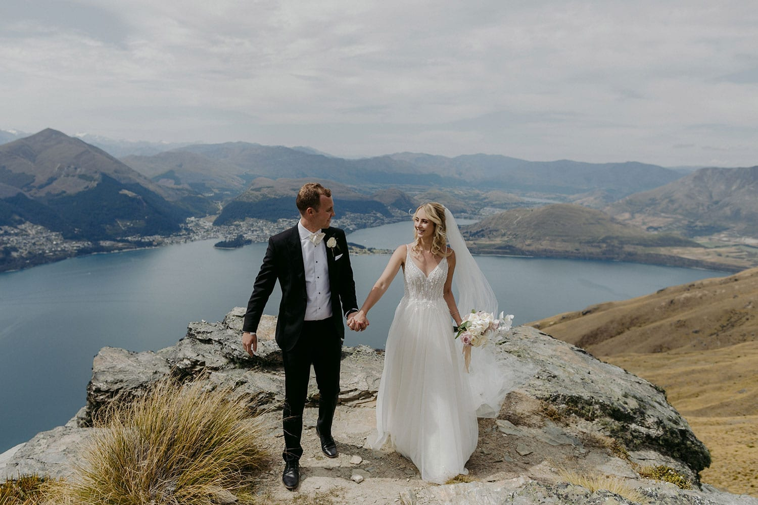 Vinka Design Features Real Weddings - bride in custom made Keiko gown from the Oriental affair collection with additional delicate dimensional flower lace added to the bodice and beading added to the skirt layers. Bride and groom on the cliffs of Lake Hays