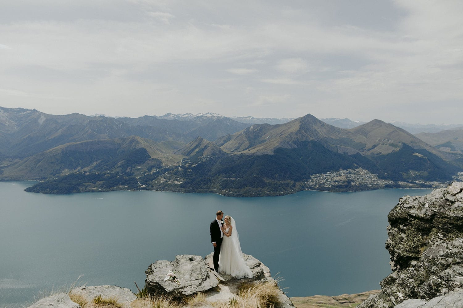 Vinka Design Features Real Weddings - bride in custom made Keiko gown from the Oriental affair collection with additional delicate dimensional flower lace added to the bodice and beading added to the skirt layers. Bride and groom on the cliffs with Lake Hays in the background
