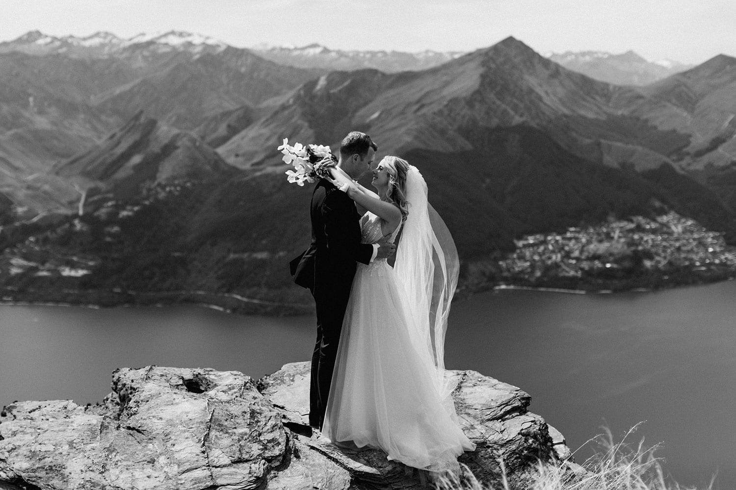Vinka Design Features Real Weddings - bride in custom made Keiko gown from the Oriental affair collection with additional delicate dimensional flower lace added to the bodice and beading added to the skirt layers. Bride and groom on the cliffs with Lake Hays in the background - black and white