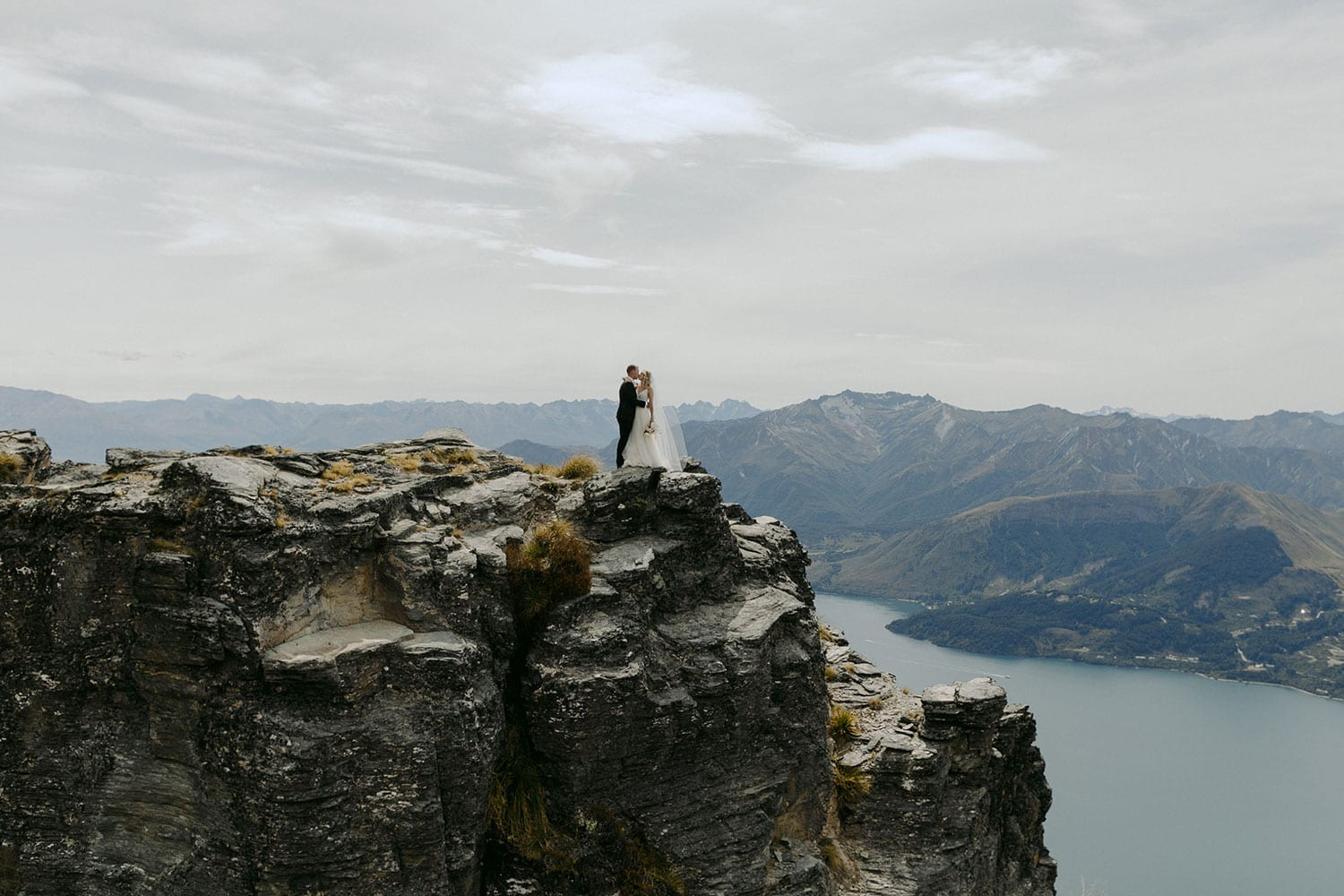 Vinka Design Features Real Weddings - bride in custom made Keiko gown from the Oriental affair collection with additional delicate dimensional flower lace added to the bodice and beading added to the skirt layers. Bride and groom embrace on the cliffs with Lake Hays in the background