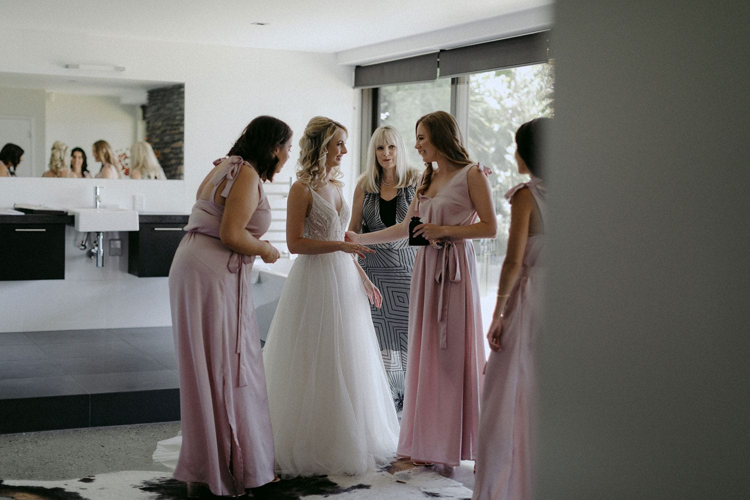 Vinka Design Features Real Weddings - bride in custom made Keiko gown from the Oriental affair collection with additional delicate dimensional flower lace added to the bodice and beading added to the skirt layers. Bride getting ready with bridesmaids