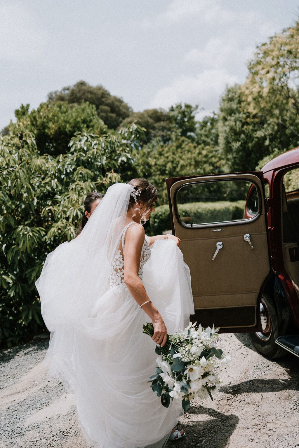 Vinka Design Features Real Weddings - bride in custom version of the Isabelle gown from our Heart of Havana collection. A fitted nude based bodice with delicate 3D beaded flowers with hand beaded trim and a skirt of dreamy tulle. Bride getting into wedding car