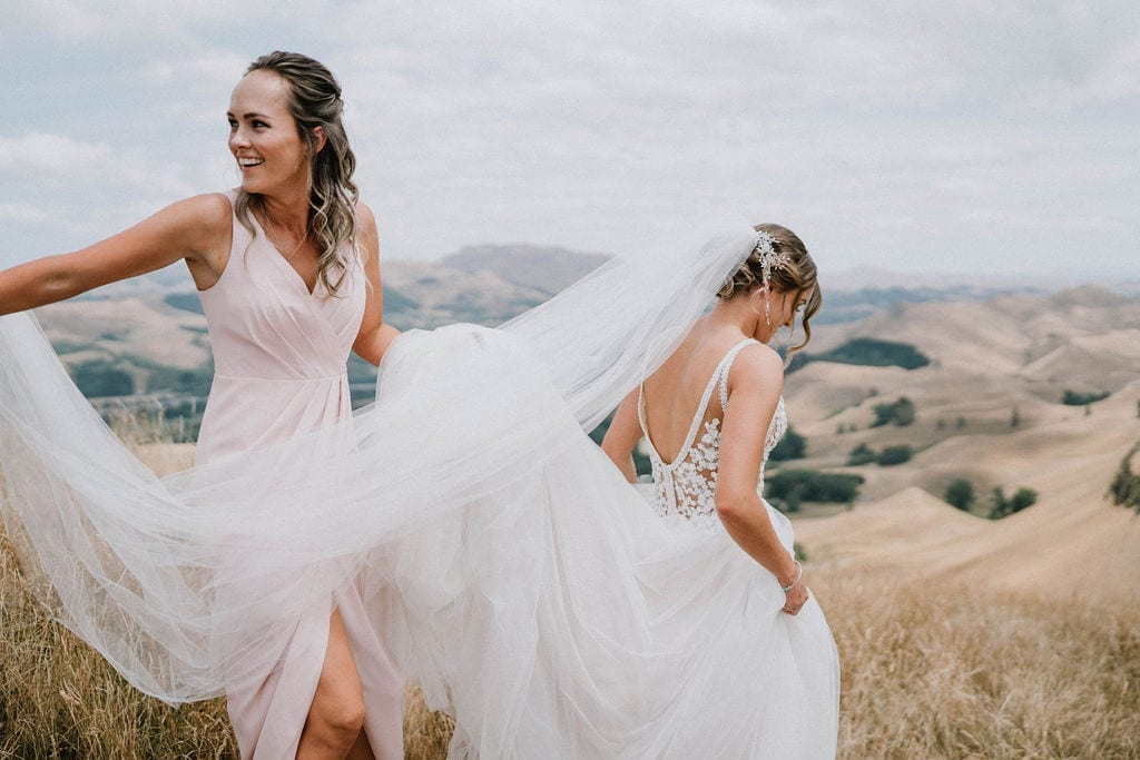 Vinka Design Features Real Weddings - bride in custom version of the Isabelle gown from our Heart of Havana collection. A fitted nude based bodice with delicate 3D beaded flowers with hand beaded trim and a skirt of dreamy tulle. Bride having train and veil held by bridesmaid