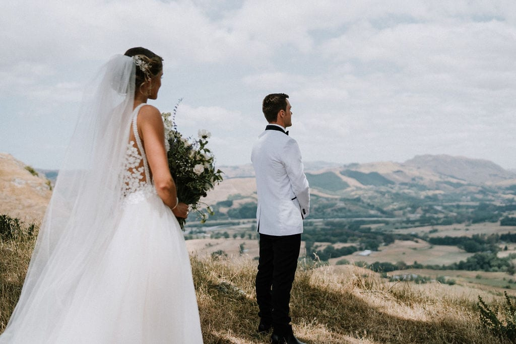 Vinka Design Features Real Weddings - bride in custom version of the Isabelle gown from our Heart of Havana collection. A fitted nude based bodice with delicate 3D beaded flowers with hand beaded trim and a skirt of dreamy tulle. Bride and groom standing on panoramic mountain