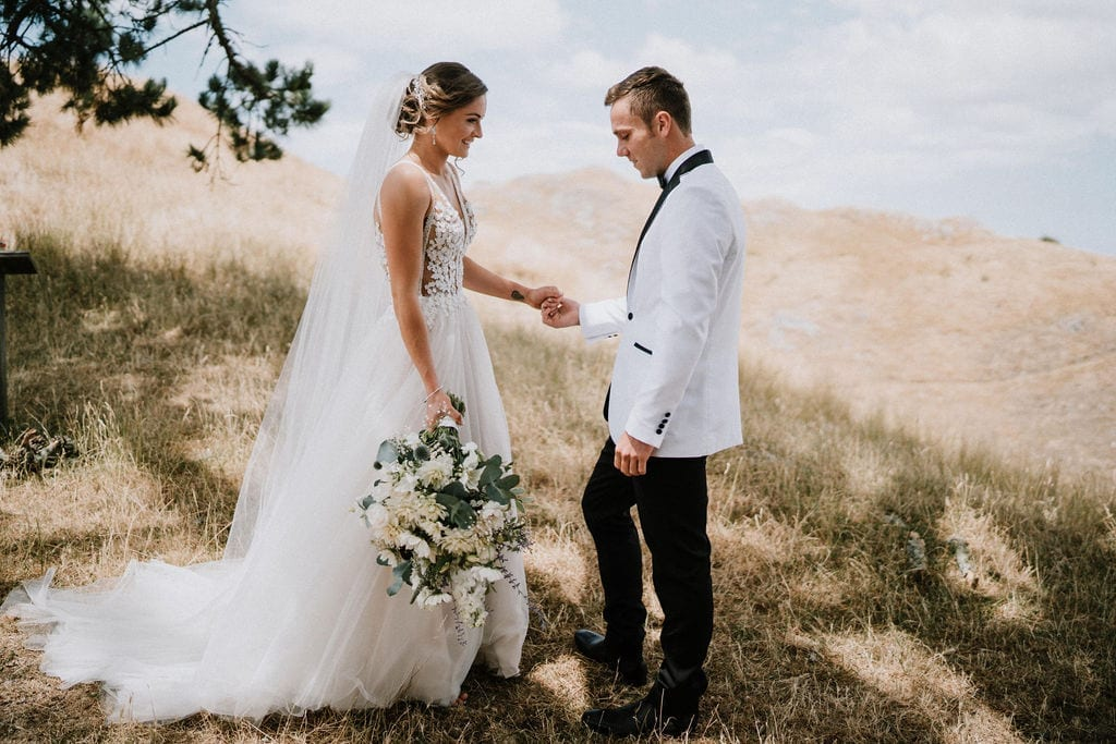 Vinka Design Features Real Weddings - bride in custom version of the Isabelle gown from our Heart of Havana collection. A fitted nude based bodice with delicate 3D beaded flowers with hand beaded trim and a skirt of dreamy tulle. Bride and groom standing together on panoramic mountain