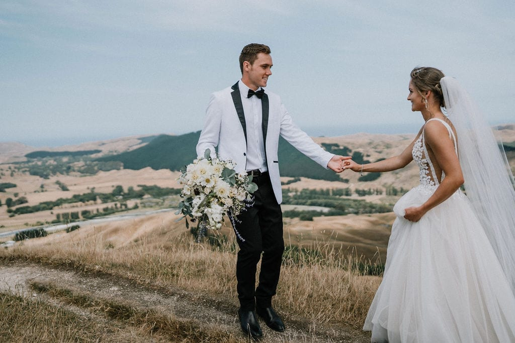 Vinka Design Features Real Weddings - bride in custom version of the Isabelle gown from our Heart of Havana collection. A fitted nude based bodice with delicate 3D beaded flowers with hand beaded trim and a skirt of dreamy tulle. Bride and groom hand in hand - nz