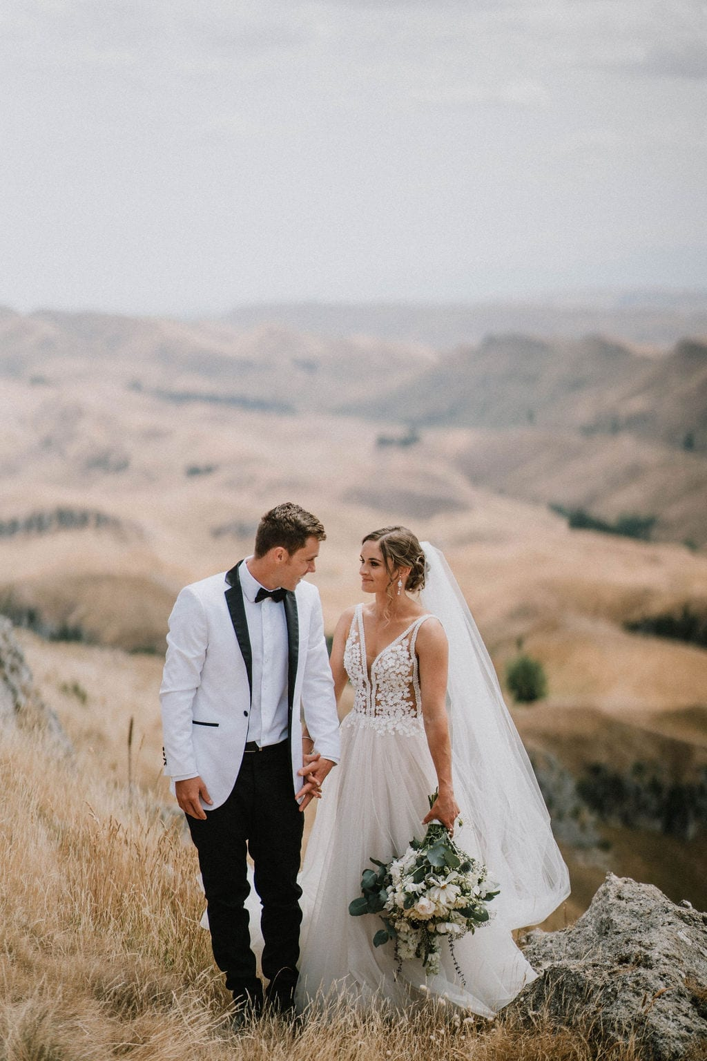 Vinka Design Features Real Weddings - bride in custom version of the Isabelle gown from our Heart of Havana collection. A fitted nude based bodice with delicate 3D beaded flowers with hand beaded trim and a skirt of dreamy tulle. Bride and groom walk hand in hand up hill - with breathtaking backdrop nz
