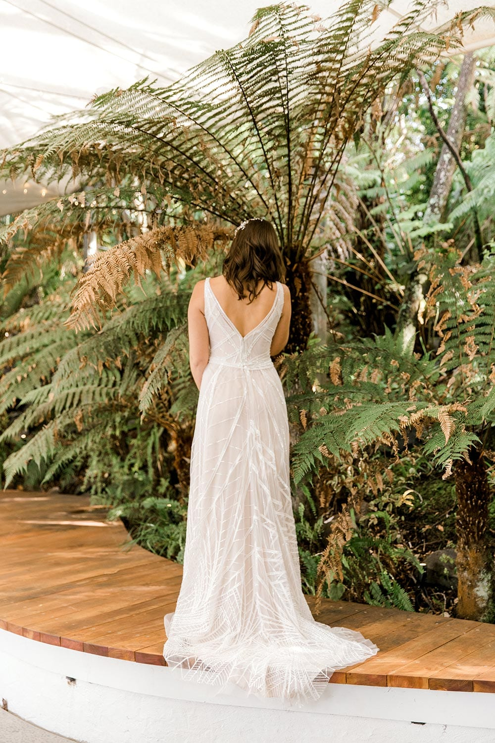 Amber Wedding Dress from Vinka Design. Beautiful wedding dress with V-neckline bodice & V-shaped back on a soft blush/light nude base. Rich beading sculpts the waist & relaxed-fit skirt falls to a train. Full length of dress from the back. Photographed at Tui Hills by Emmaline Photography.