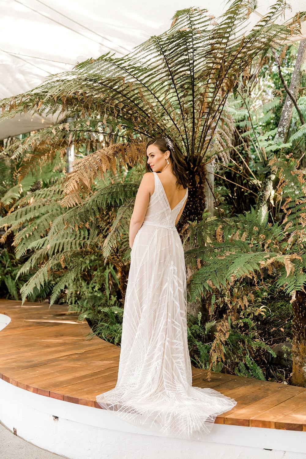 Amber Wedding Dress from Vinka Design. Beautiful wedding dress with V-neckline bodice & V-shaped back on a soft blush/light nude base. Rich beading sculpts the waist & relaxed-fit skirt falls to a train. Full length of dress from the side. Photographed at Tui Hills by Emmaline Photography.