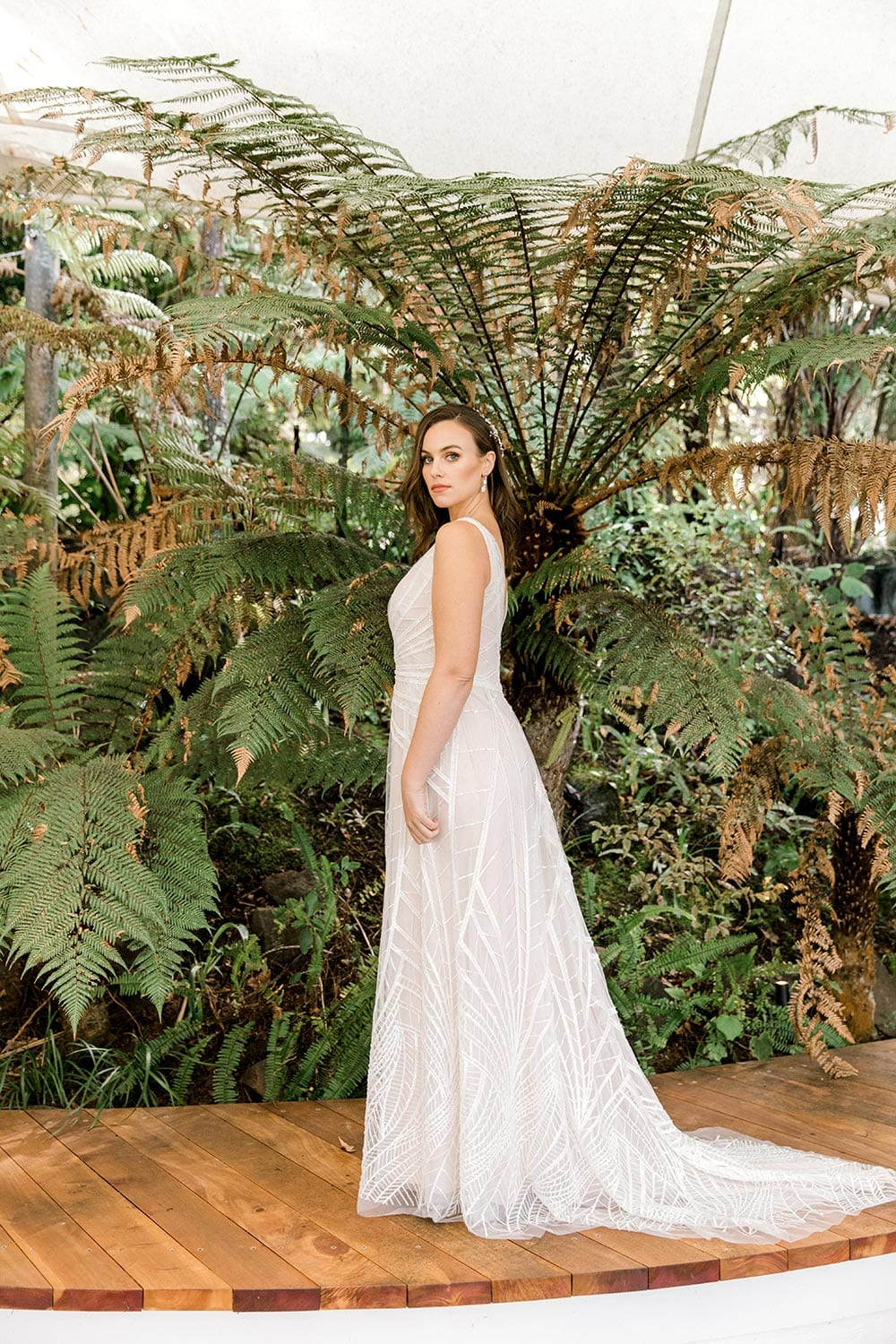 Amber Wedding Dress from Vinka Design. Beautiful wedding dress with V-neckline bodice & V-shaped back on a soft blush/light nude base. Rich beading sculpts the waist & relaxed-fit skirt falls to a train. Full length of dress with train flowing to the ground. Photographed at Tui Hills by Emmaline Photography.