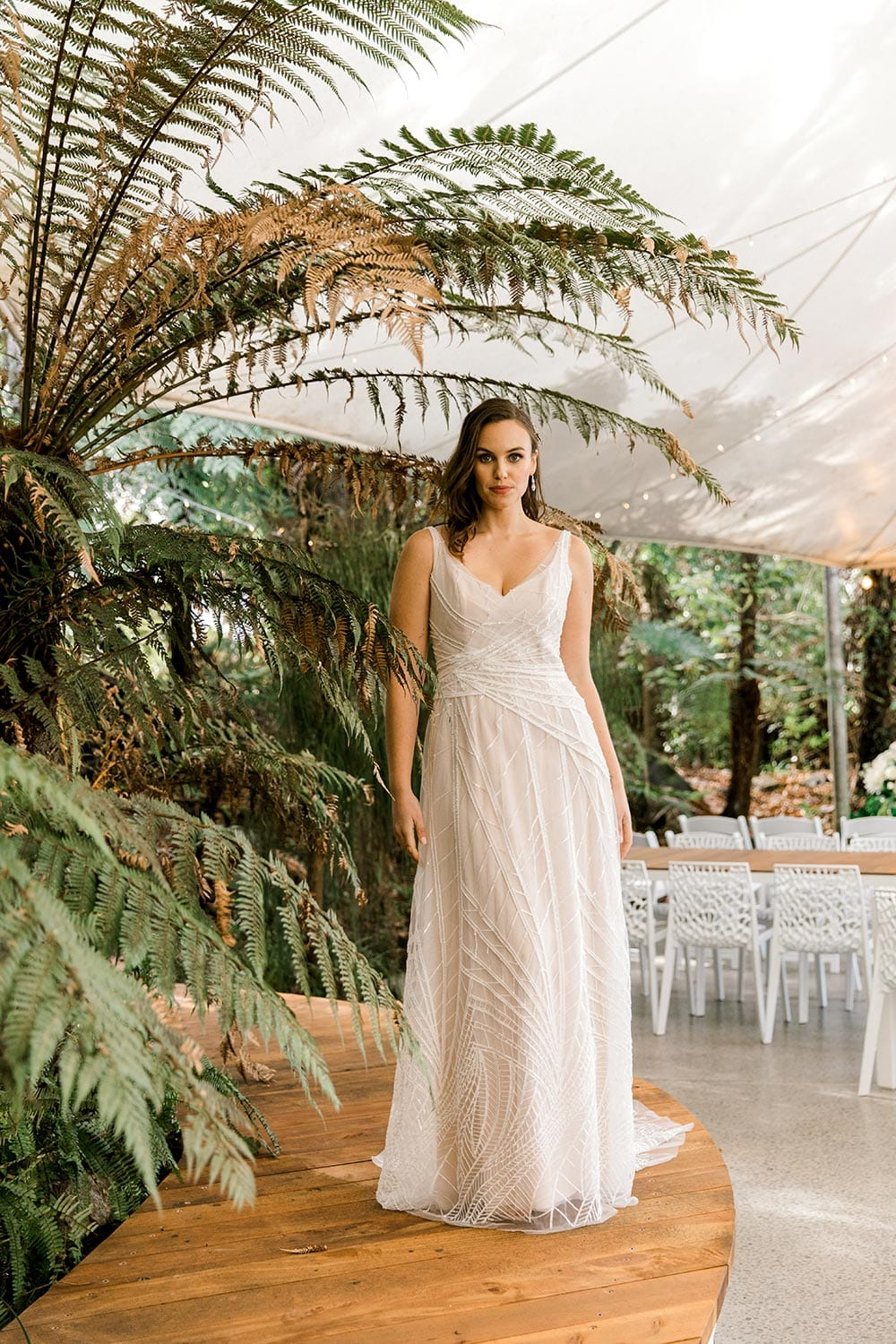 Amber Wedding Dress from Vinka Design. Beautiful wedding dress with V-neckline bodice & V-shaped back on a soft blush/light nude base. Rich beading sculpts the waist & relaxed-fit skirt falls to a train. Full length of dress from the front. Photographed at Tui Hills by Emmaline Photography.