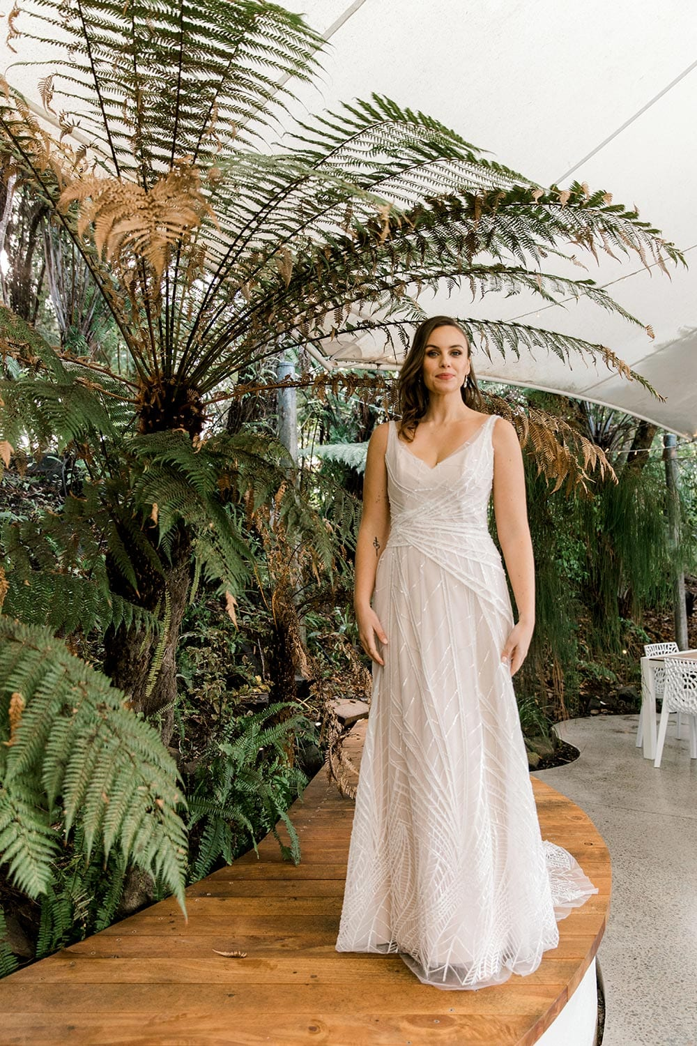 Amber Wedding Dress from Vinka Design. Beautiful wedding dress with V-neckline bodice & V-shaped back on a soft blush/light nude base. Rich beading sculpts the waist & relaxed-fit skirt falls to a train. Full length of dress front. Photographed at Tui Hills by Emmaline Photography.