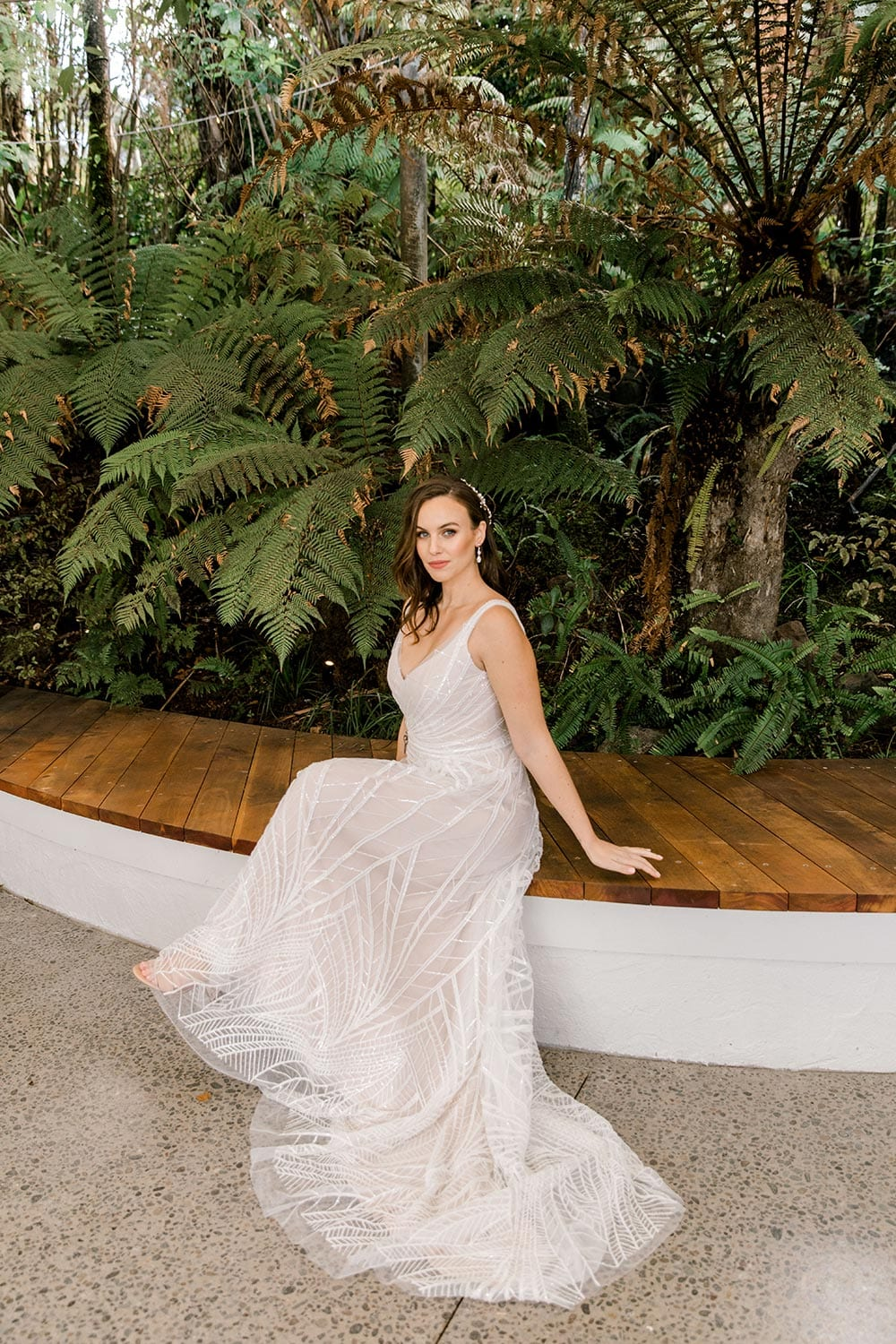 Amber Wedding Dress from Vinka Design. Beautiful wedding dress with V-neckline bodice & V-shaped back on a soft blush/light nude base. Rich beading sculpts the waist & relaxed-fit skirt falls to a train. Model sitting, dress flowing to the ground. Photographed at Tui Hills by Emmaline Photography.