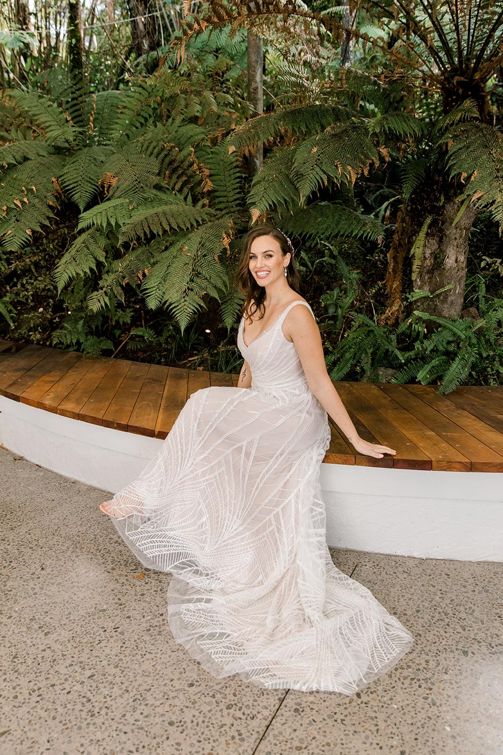 Amber Wedding Dress from Vinka Design. Beautiful wedding dress with V-neckline bodice & V-shaped back on a soft blush/light nude base. Rich beading sculpts the waist & relaxed-fit skirt falls to a train. Model sitting, dress and train flowing to the ground. Photographed at Tui Hills by Emmaline Photography.