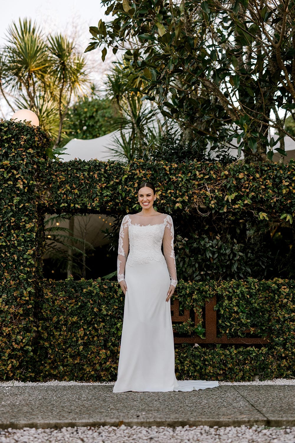 Ariel Wedding Dress from Vinka Design. Wedding dress with illusion scoop neckline & sheer low back with beaded lace. Long, fitted lace sleeves with pearl buttons & A-line skirt that falls into a train. Full length dress portrait, photographed at Tui Hills by Emmaline Photography.