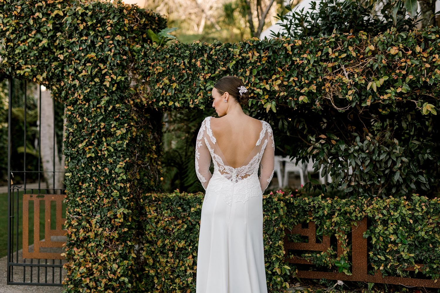 Ariel Wedding Dress from Vinka Design. Wedding dress with illusion scoop neckline & sheer low back with beaded lace. Long, fitted lace sleeves with pearl buttons & A-line skirt that falls into a train. Detail of dress from the back, photographed at Tui Hills by Emmaline Photography.