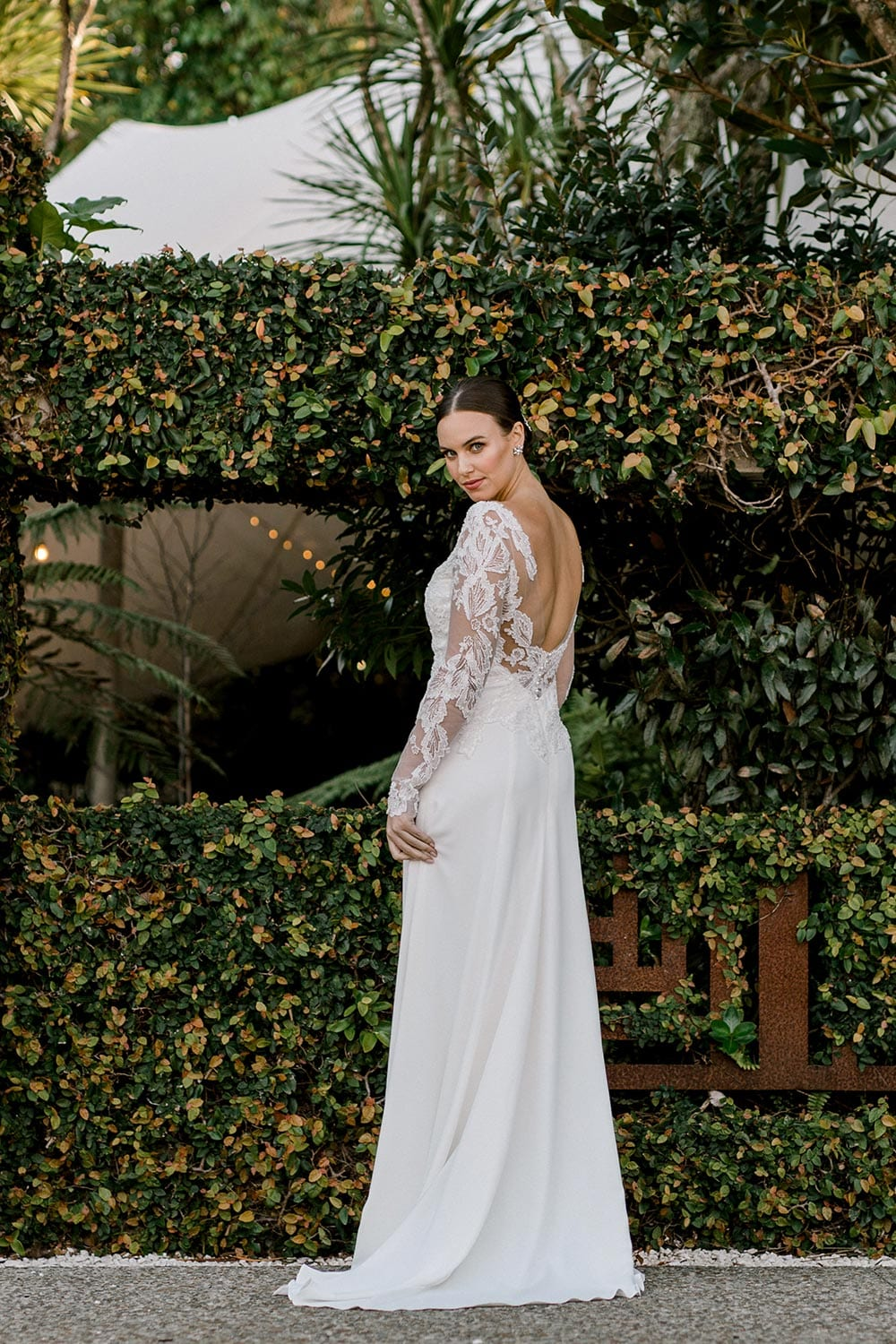 Ariel Wedding Dress from Vinka Design. Wedding dress with illusion scoop neckline & sheer low back with beaded lace. Long, fitted lace sleeves with pearl buttons & A-line skirt that falls into a train. Full length dress detail to the side, photographed at Tui Hills by Emmaline Photography.