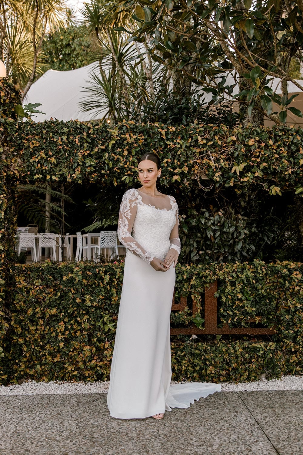 Ariel Wedding Dress from Vinka Design. Wedding dress with illusion scoop neckline & sheer low back with beaded lace. Long, fitted lace sleeves with pearl buttons & A-line skirt that falls into a train. full length dress, photographed at Tui Hills by Emmaline Photography.