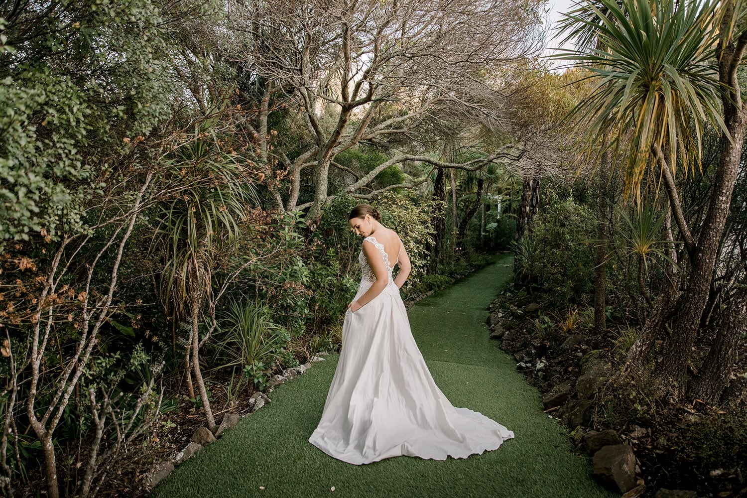 Ashleigh Wedding Dress from Vinka Design. Wedding dress with semi-sheer, richly embroidered fitted bodice on a nude base adorned with guipure lace. Dramatic silk dupion full skirt with side pockets. Dress from back with hands in pockets, photographed at Tui Hills by Emmaline Photography.