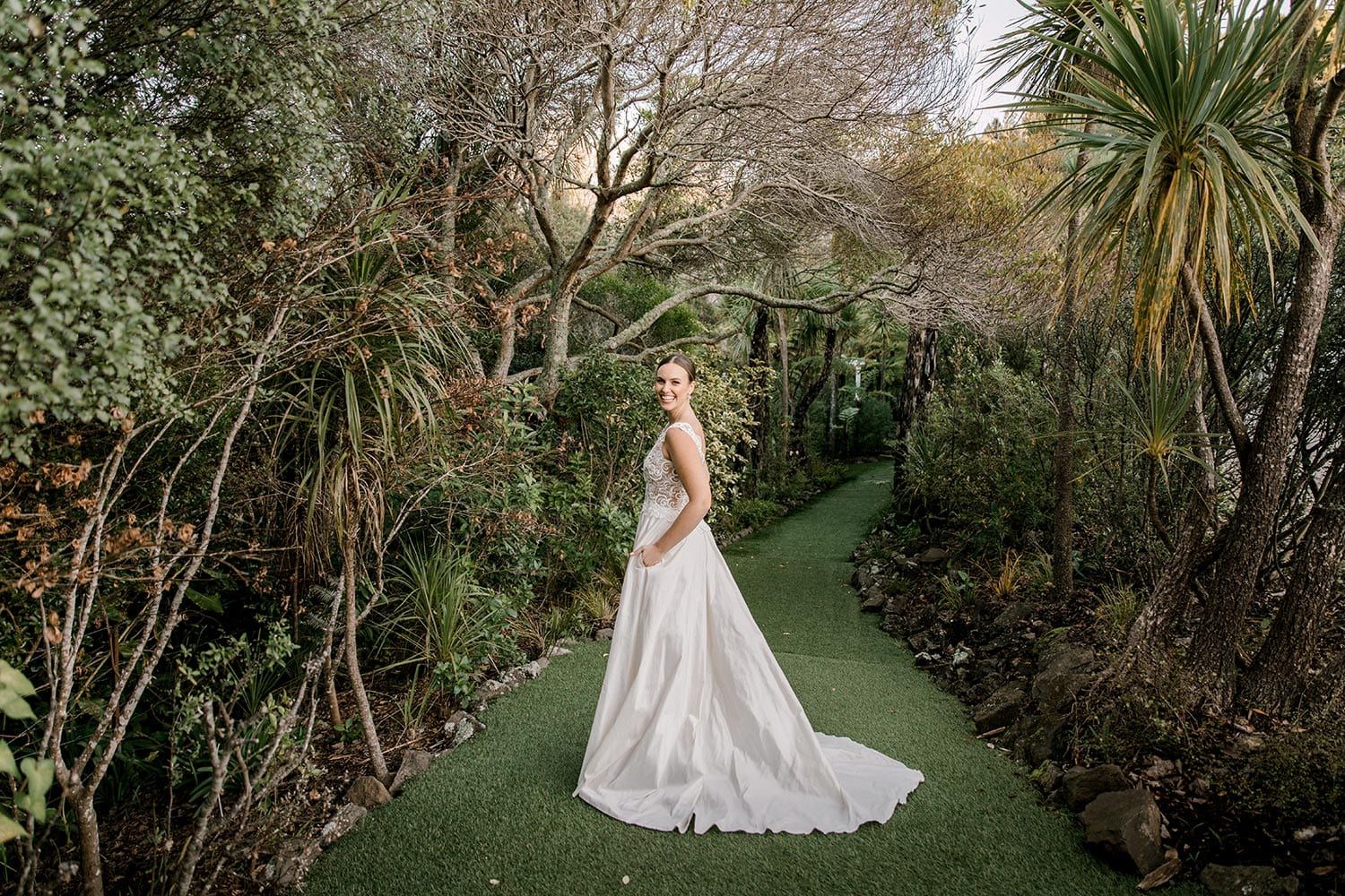 Ashleigh Wedding Dress from Vinka Design. Wedding dress with semi-sheer, richly embroidered fitted bodice on a nude base adorned with guipure lace. Dramatic silk dupion full skirt with side pockets. Dress from side with hands in pockets, photographed at Tui Hills by Emmaline Photography.