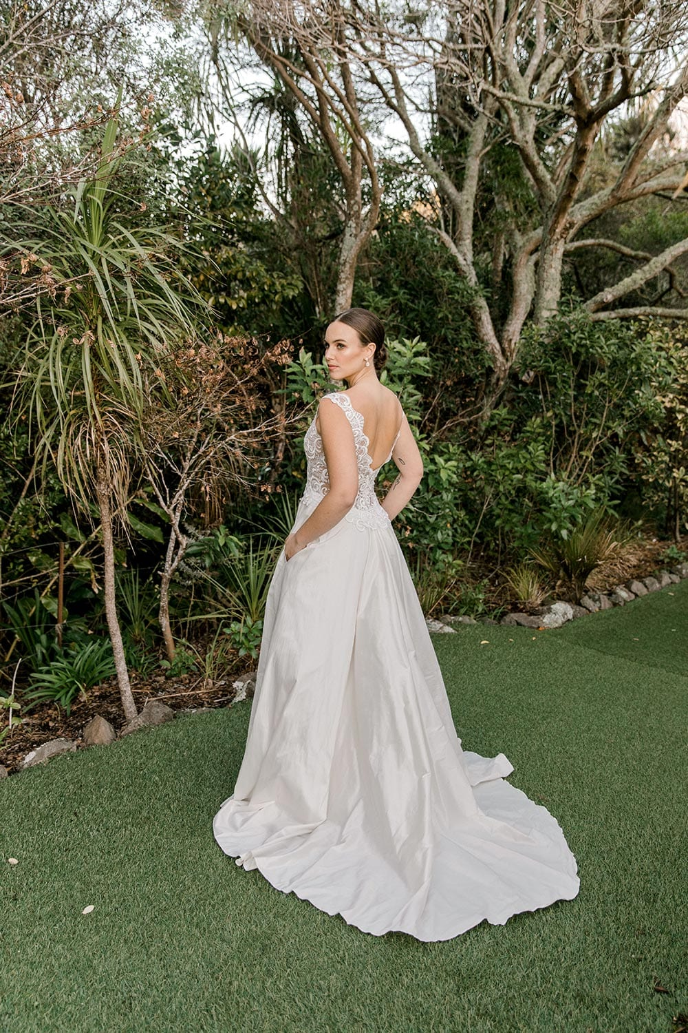 Ashleigh Wedding Dress from Vinka Design. Wedding dress with semi-sheer, richly embroidered fitted bodice on a nude base adorned with guipure lace. Dramatic silk dupion full skirt with side pockets. Dress back detail with flowing skirt, photographed at Tui Hills by Emmaline Photography.