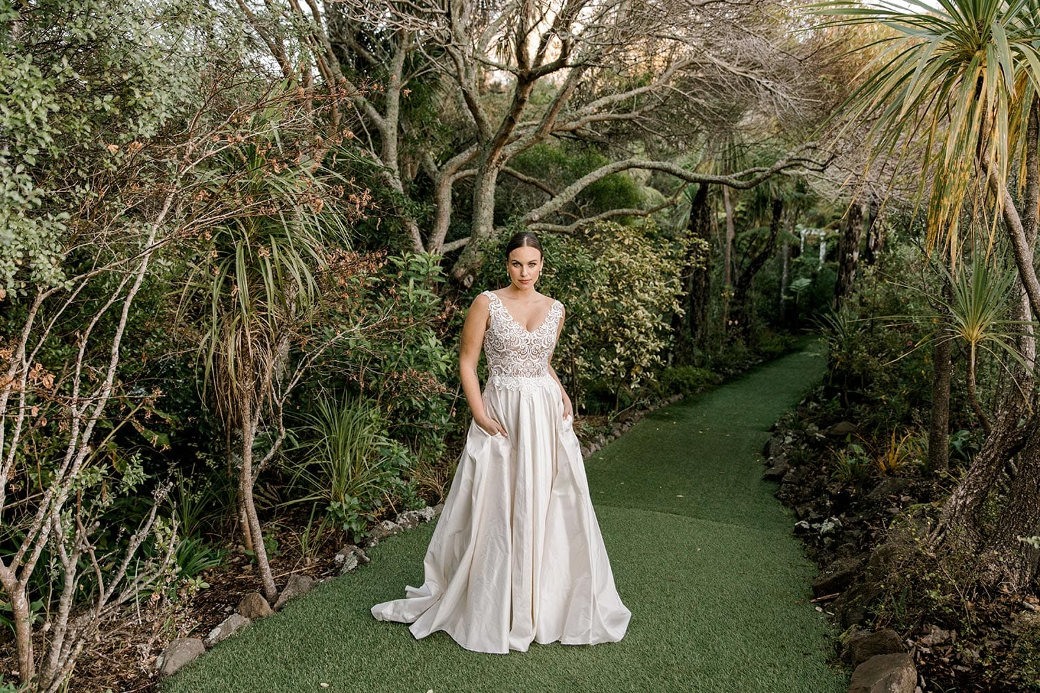 Ashleigh Wedding Dress from Vinka Design. Wedding dress with semi-sheer, richly embroidered fitted bodice on a nude base adorned with guipure lace. Dramatic silk dupion full skirt with side pockets. Full length dress portrait, photographed at Tui Hills by Emmaline Photography.
