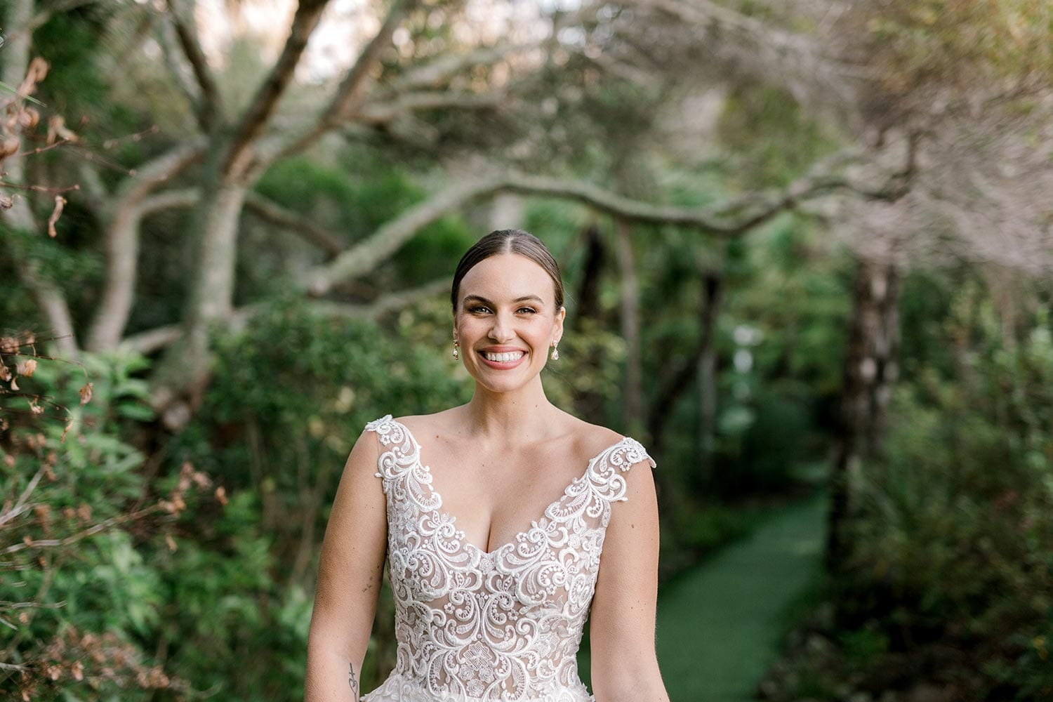 Ashleigh Wedding Dress from Vinka Design. Wedding dress with semi-sheer, richly embroidered fitted bodice on a nude base adorned with guipure lace. Dramatic silk dupion full skirt with side pockets. Close up detail of bodice, photographed at Tui Hills by Emmaline Photography.