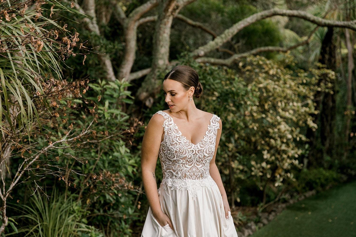 Ashleigh Wedding Dress from Vinka Design. Wedding dress with semi-sheer, richly embroidered fitted bodice on a nude base adorned with guipure lace. Dramatic silk dupion full skirt with side pockets. Close up detail of bodice with hands in skirt pockets, photographed at Tui Hills by Emmaline Photography.