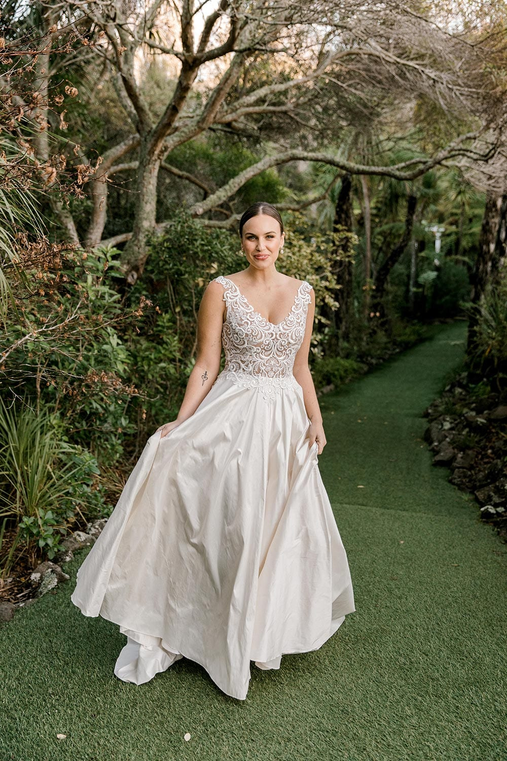 Ashleigh Wedding Dress from Vinka Design. Wedding dress with semi-sheer, richly embroidered fitted bodice on a nude base adorned with guipure lace. Dramatic silk dupion full skirt with side pockets. Full length dress portrait with skirt held, photographed at Tui Hills by Emmaline Photography.