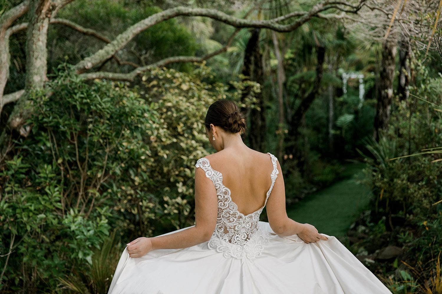 Ashleigh Wedding Dress from Vinka Design. Wedding dress with semi-sheer, richly embroidered fitted bodice on a nude base adorned with guipure lace. Dramatic silk dupion full skirt with side pockets. Dress from behind with skirt held out, photographed at Tui Hills by Emmaline Photography.