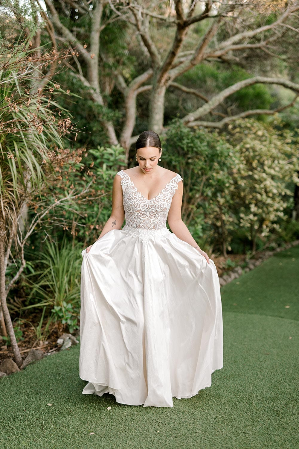 Ashleigh Wedding Dress from Vinka Design. Wedding dress with semi-sheer, richly embroidered fitted bodice on a nude base adorned with guipure lace. Dramatic silk dupion full skirt with side pockets. Full length dress portrait with hands in pockets showing skirt layers, photographed at Tui Hills by Emmaline Photography.