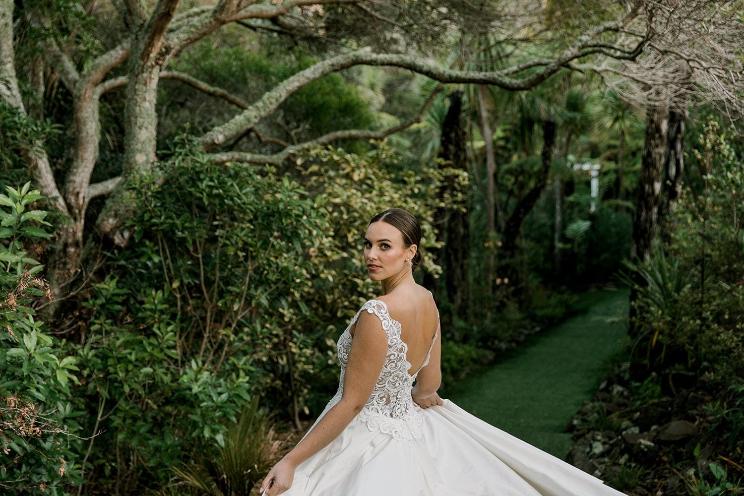 Ashleigh Wedding Dress from Vinka Design. Wedding dress with semi-sheer, richly embroidered fitted bodice on a nude base adorned with guipure lace. Dramatic silk dupion full skirt with side pockets. Dress from side with skirt held out, photographed at Tui Hills by Emmaline Photography.