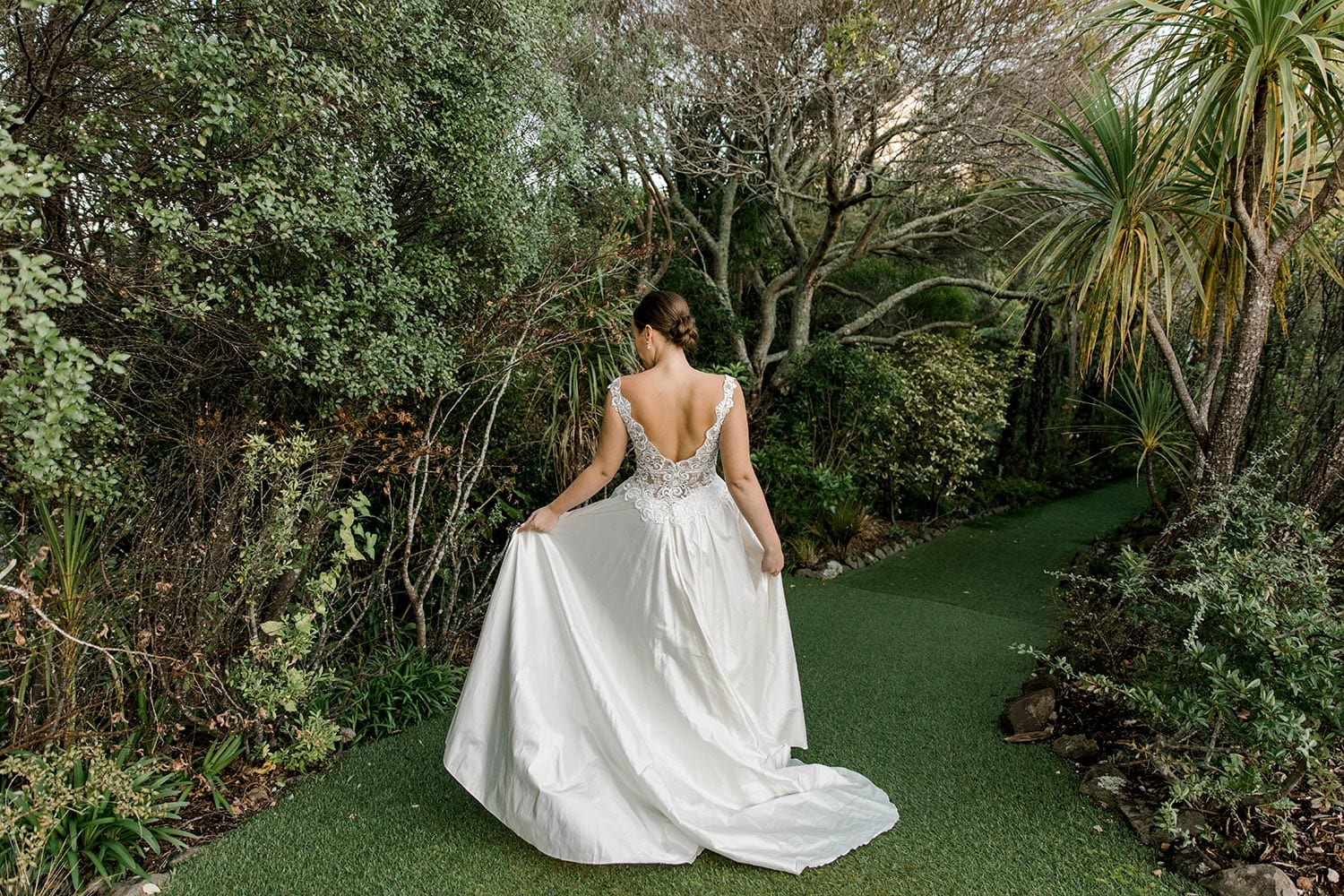 Ashleigh Wedding Dress from Vinka Design. Wedding dress with semi-sheer, richly embroidered fitted bodice on a nude base adorned with guipure lace. Dramatic silk dupion full skirt with side pockets. Dress from behind with model walking away, photographed at Tui Hills by Emmaline Photography.