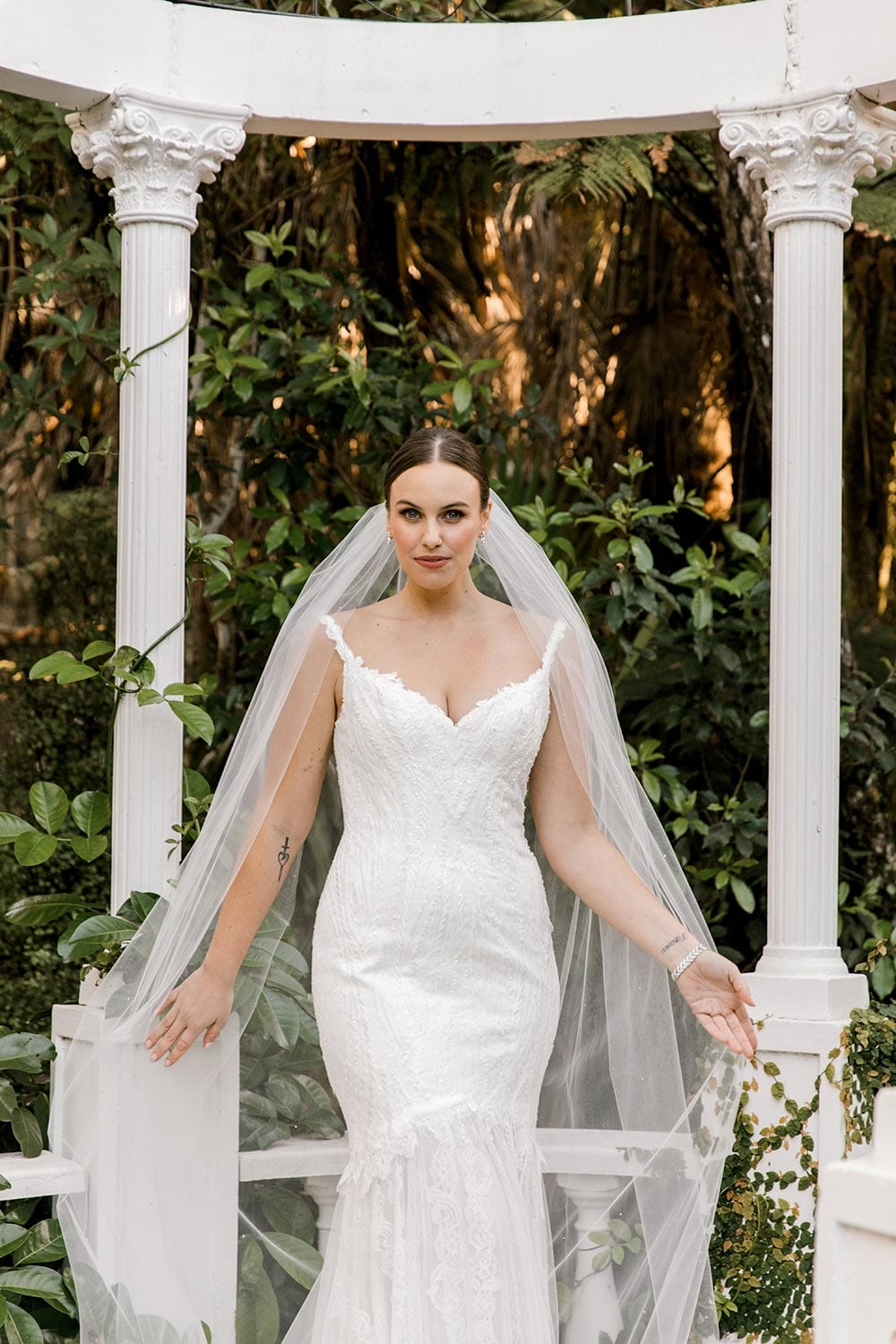 Brooke Wedding Dress from Vinka Design. This stunning wedding dress has a structured bodice intricately layered to emphasize natural curves. Sweetheart neckline, delicate lace-embellished straps, low back & silk chiffon train. Front of dress portrait, photographed at Tui Hills by Emmaline Photography.