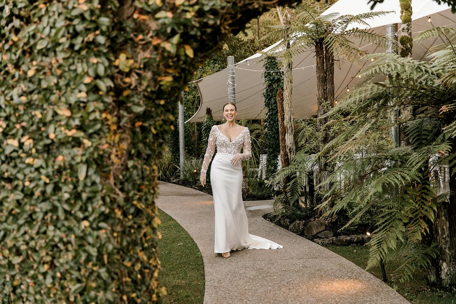 Celeste Wedding Dress from Vinka Design. Gorgeous form fitting stretch fabric wedding dress. The bodice is nude & semi-sheer, featuring 3-D beaded leaf lace, a deep V-neckline and a low V-shaped back with long sleeves. Model walking through archway, photographed at Tui Hills by Emmaline Photography.