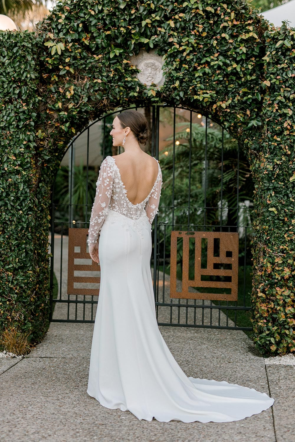Celeste Wedding Dress from Vinka Design. Gorgeous form fitting stretch fabric wedding dress. The bodice is nude & semi-sheer, featuring 3-D beaded leaf lace, a deep V-neckline and a low V-shaped back with long sleeves. Full length portrait of back of dress, photographed at Tui Hills by Emmaline Photography.