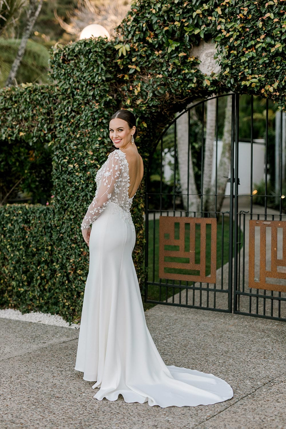Celeste Wedding Dress from Vinka Design. Gorgeous form fitting stretch fabric wedding dress. The bodice is nude & semi-sheer, featuring 3-D beaded leaf lace, a deep V-neckline and a low V-shaped back with long sleeves. Full length portrait of side of dress with train to the back, photographed at Tui Hills by Emmaline Photography.