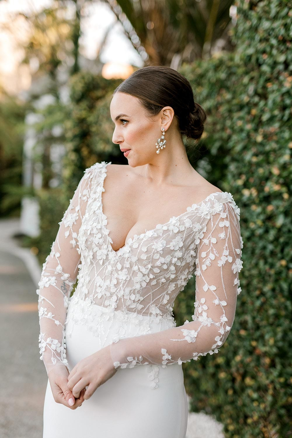 Celeste Wedding Dress from Vinka Design. Gorgeous form fitting stretch fabric wedding dress. The bodice is nude & semi-sheer, featuring 3-D beaded leaf lace, a deep V-neckline and a low V-shaped back with long sleeves. Close up detail of bodice, photographed at Tui Hills by Emmaline Photography.