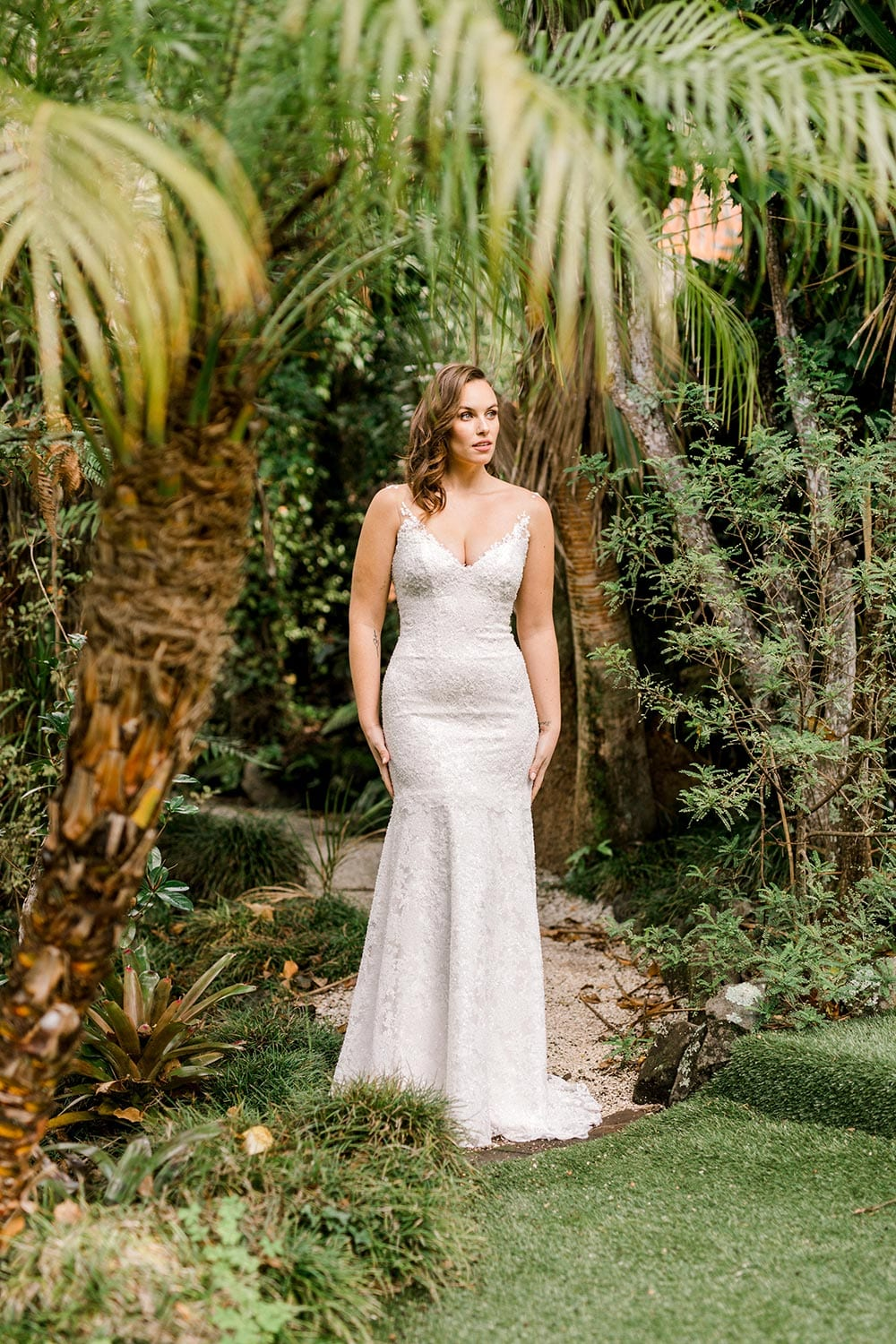 Dakota Wedding Dress from Vinka Design. This full-lace wedding dress is form fitting, sculpting the body beautifully. Delicate beaded lace flowers are hand-appliqued up the sheer nude tulle straps on both the front & back. Full length portrait of gown, photographed at Tui Hills by Emmaline Photography.
