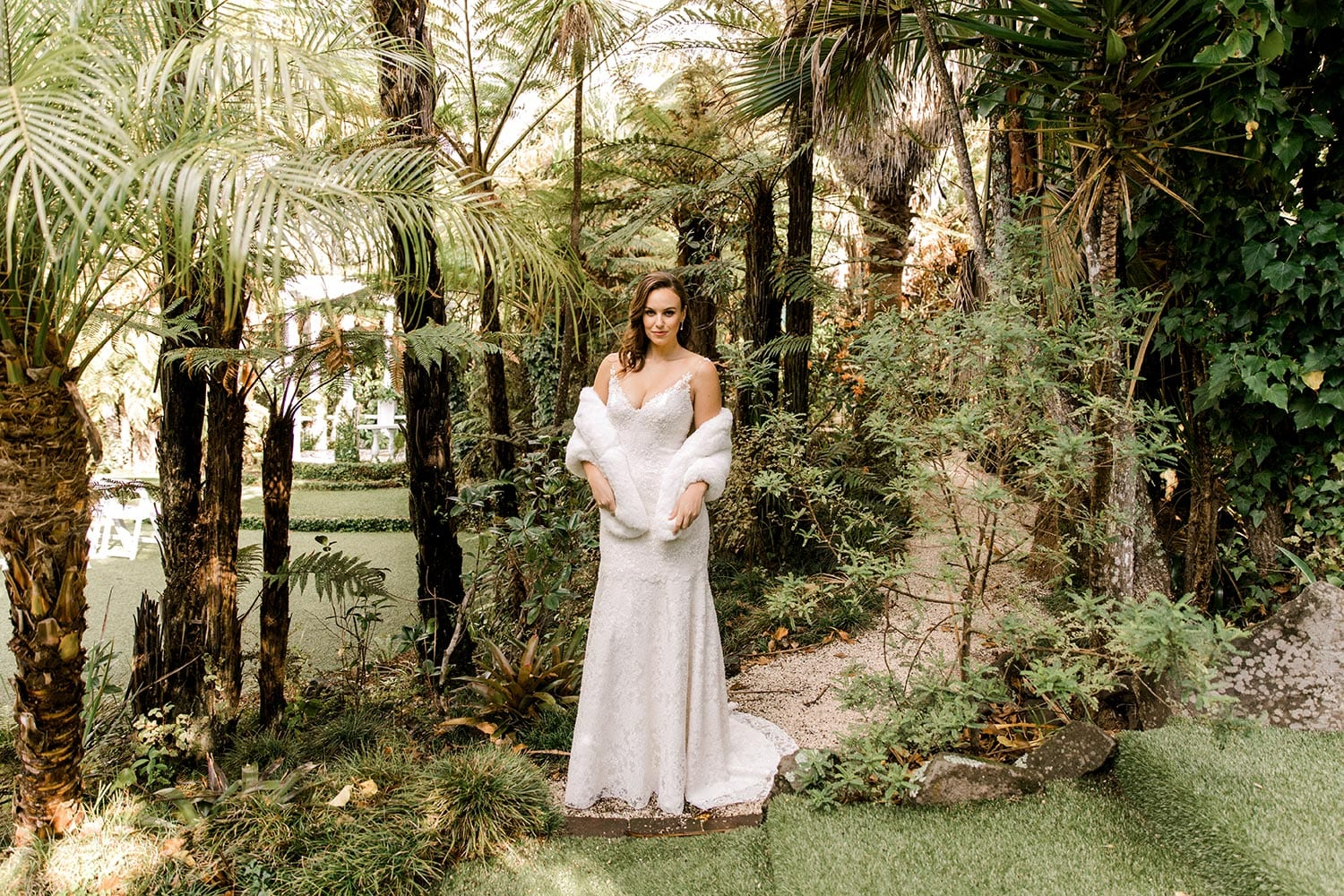 Dakota Wedding Dress from Vinka Design. This full-lace wedding dress is form fitting, sculpting the body beautifully. Delicate beaded lace flowers are hand-appliqued up the sheer nude tulle straps on both the front & back. Landscape of full length dress worn with snug, photographed at Tui Hills by Emmaline Photography.